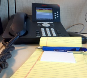 desk at an office with a phone and note pad